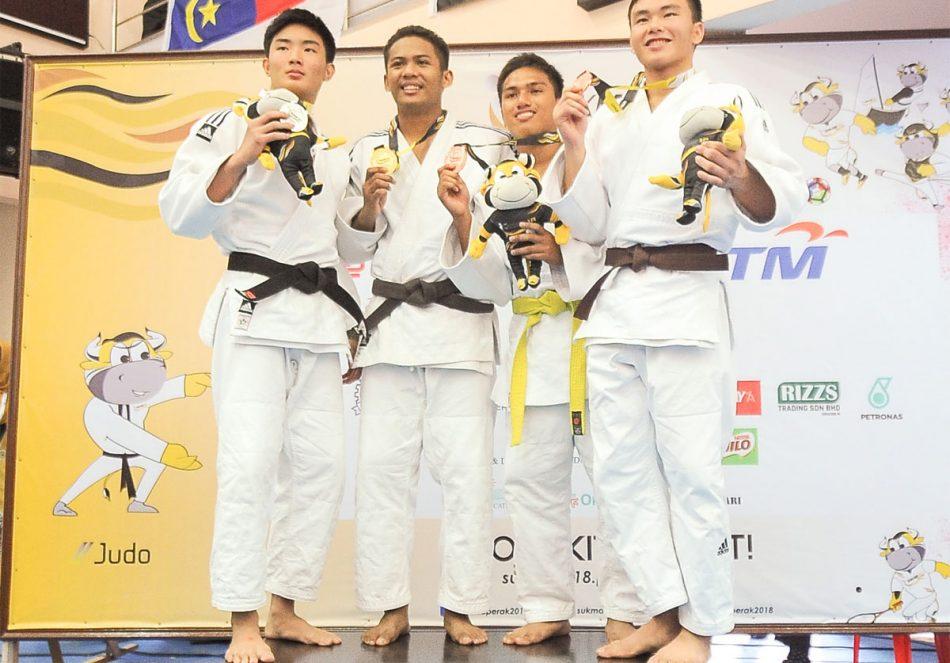 Mohamad Aizul Hilmi bin Zainudin(dua dari kiri) menyumbang pingat emas kepada kontijen Terengganu Hanelang setelah berentap dalam kategori lelaki bawah 73kg akhir menewaskan judoka Pulau Pinang; Chan Por Hao(kiri) di hari pertama kejohanan judo Sukan Malaysia(SUKMA) Perak 2018 yang telah berlansung di Dewan SMJK Krian, Kerian. Kredit Foto - Sekretariat SUKMA Perak 2018