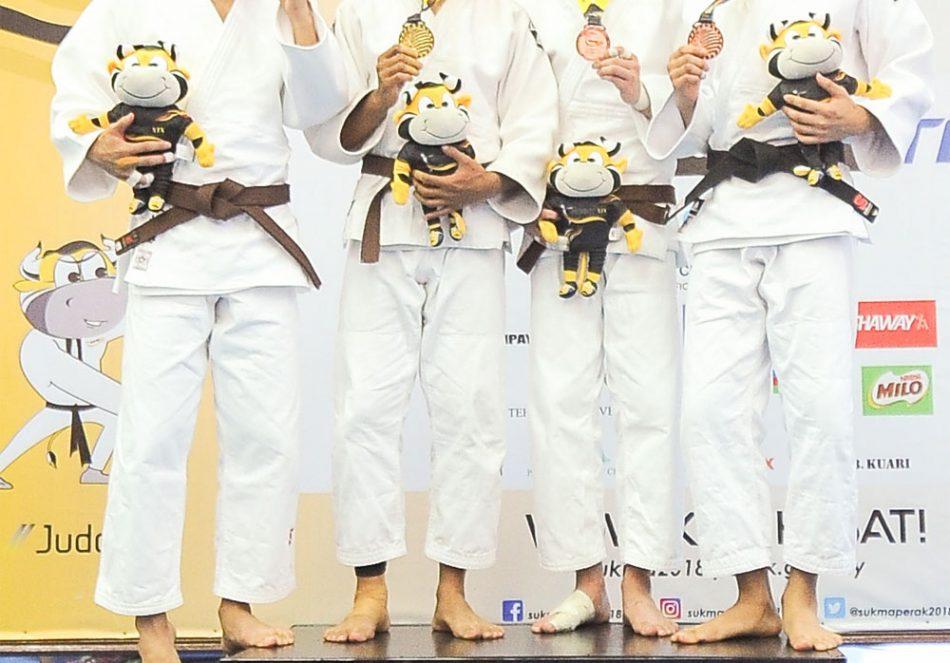 Muhammad Izham bin Harun(dua dari kiri) menyumbang pingat emas kepada kontijen Terengganu Hanelang setelah berentap dalam kategori lelaki bawah 60kg menewaskan judoka Negeri Sembilan; Toh Wei Sheng(kiri) di hari pertama kejohanan judo Sukan Malaysia(SUKMA) Perak 2018 yang telah berlansung di Dewan SMJK Krian, Kerian. Kredit Foto - Sekretariat SUKMA Perak 2018