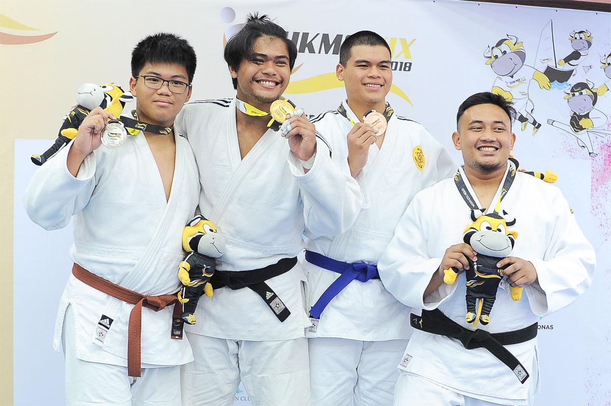 Fakhrul Adam bin Jose M Cruz @ Fauzi Cruz(dua dari kiri) menyumbang pingat emas kepada kontijen Terengganu Hanelang setelah berentap dalam kategori lelaki bawah 90kg akhir. Judoka Pulau Pinang; Tan Tze Ning(kiri) meraih pingat perak manakala judoka Selangor; Ezzam bin Mohd Azmurin(tiga dari kiri) dan judoka Johor Ahmad Zikri bin Abd Rashid berkongsi gangsa di hari kedua kejohanan judo Sukan Malaysia(SUKMA) Perak 2018 yang telah berlansung di Dewan SMJK Krian, Kerian. Kredit Foto - Sekretariat SUKMA Perak 2018