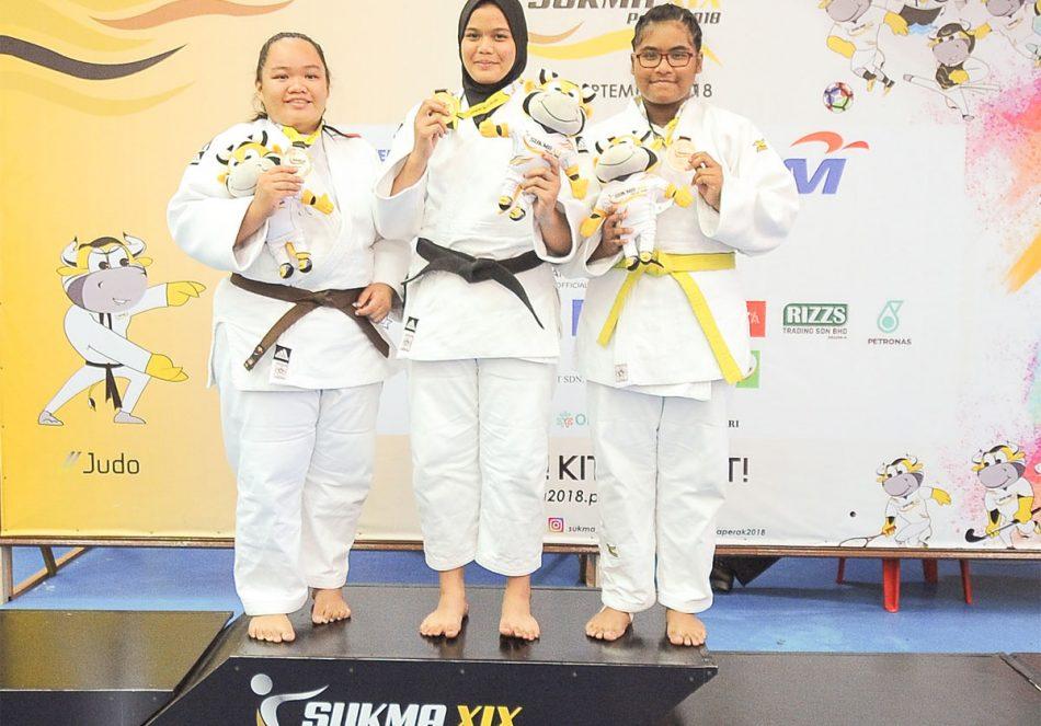 Nur Ain Hafiezza binti Amran(dua dari kiri) menyumbang pingat emas kepada kontijen Terengganu Hanelang setelah berentap dalam kategori wanita melebihi 70kg akhir. Judoka Sabah; Mel Motusin(kiri) turut berkongsi pingat emas manakala judoka tuan rumah; Aida Adriana meraih gangsa di hari pertama kejohanan judo Sukan Malaysia(SUKMA) Perak 2018 yang telah berlansung di Dewan SMJK Krian, Kerian. Kredit Foto - Sekretariat SUKMA Perak 2018