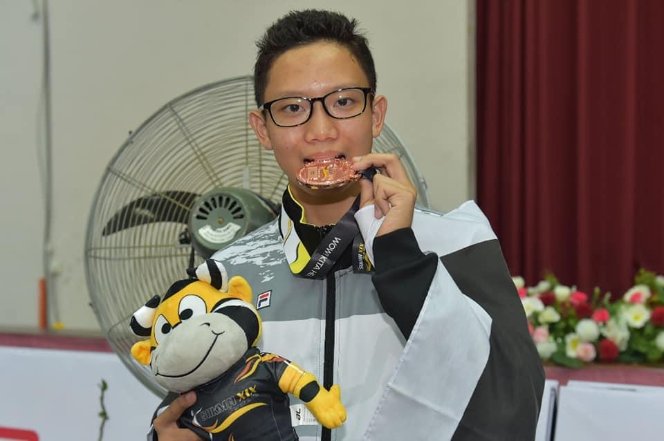 Atlet sukan wushu; Mohamad Afiq Danial bin Mohd Firdaus Chua yang berusia 16 tahun menjadi penyumbang pertama kutipan pingat buat kontijen Terengganu Hanelang setelah meraih pingat gangsa dalam acara Jianshu (pedang) dalam temasya Sukan Malaysia(SUKMA) Perak 2018. Kredit Foto - Facebook.com/govtrg