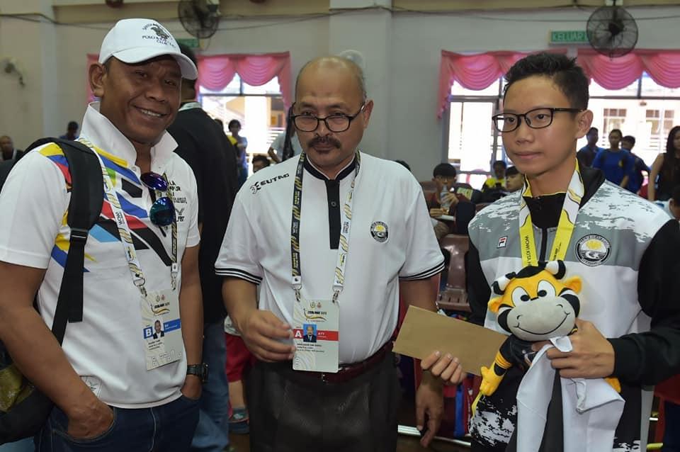 Atlet wushu negeri Terengganu; Mohamad Afiq Danial bin Mohd Firdaus Chua(tiga dari kiri) bersama Pengarah Majlis Sukan Negeri Terengganu; Encik Ibni Amin Busu(dua dari kiri) setelah berjaya merangkul pingat gangsa yang juga merupakan kutipan pingat pertama buat kontijen negeri Terengganu dalam acara Jianshu (pedang) di pentas Sukan Malaysia(SUKMA) Perak 2018 bertempat di Kolej Matrikulasi Gopeng. Kredit Foto - Facebook.com/govtrg