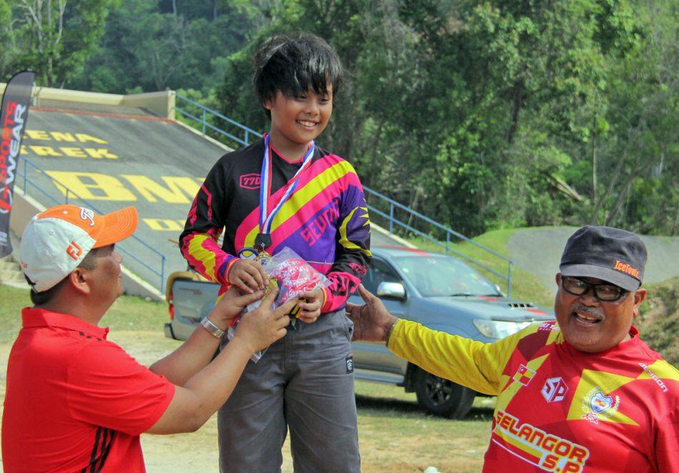 Nurkhairin Najiha dari pasukan Cyclomaniac TSSI Seven7; pelumba tunggal bagi acara perempuan bawah 12 tahun sekali gus dinobatkan selaku juara. Sepanjang perlumbaan turut mengutip pengalaman untuk berlumba bersama peserta acara perempuan bawah 15 tahun. Kredit Foto - PenyuSukan.com